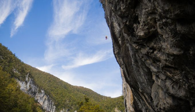 Climber abseils down huge steep wall
