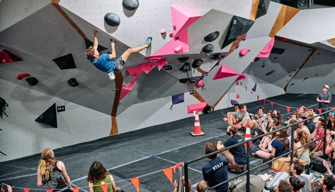 Climber on competition boulder with crowd watching