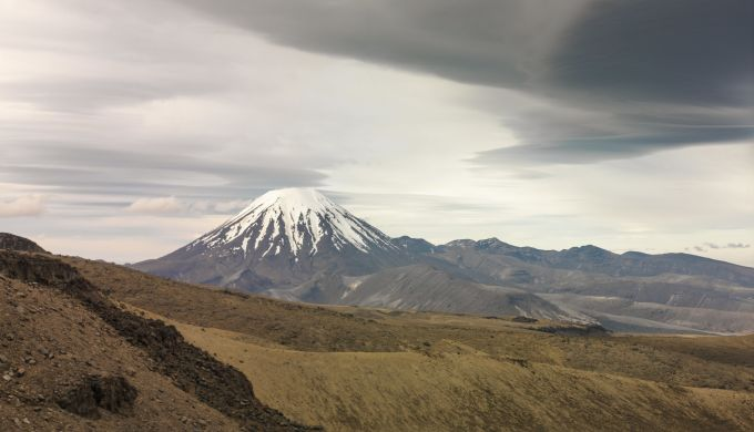 A snow-capped conical volcano with cloud formations