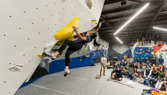 Female climbing in competition with crowd watching.