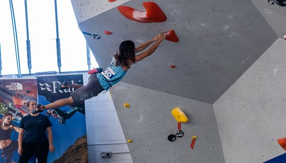 Climber moves dynamically on competition boulder wall